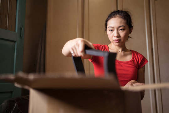 Ethnic lady unpacking carton box with disassembled chair parts after delivery in cozy room at home