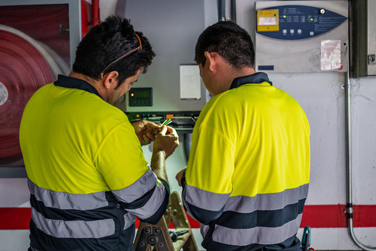 Back view of group of professional male technicians with electric tools repairing and checking equipment while working in building