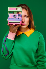 Young unemotional female in green pullover taking picture with retro instant camera while standing against green background