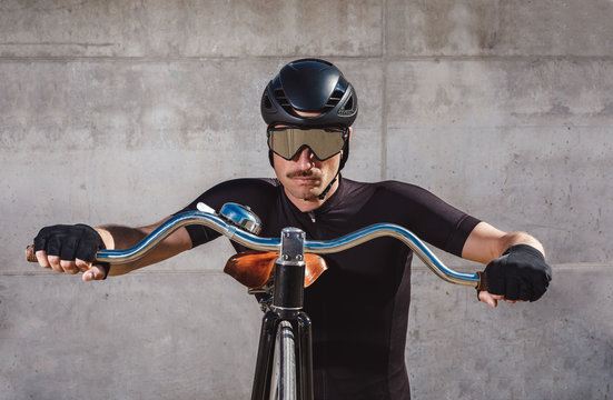 Calm determined man in black activewear and helmet looking at camera while standing on asphalt road and leaning on high wheel bicycle against concrete wall in sunny day