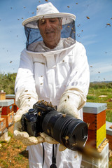 From below of beekeeper in protective costume and gloves holding professional photo camera of beehive in apiary