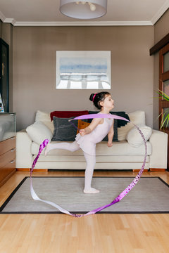 Side view of cute little girl in leotard and tights spinning ribbon and dancing during rhythmic gymnastic training in cozy living room at home