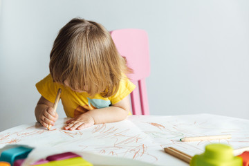 Cute little girl in yellow shirt sitting at table and drawing with colorful pencils while spending time in playroom in kindergarten