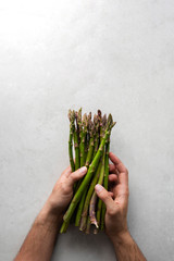 Top view of crop anonymous chef holding bunch of fresh green asparagus while preparing food at gray marble table in kitchen