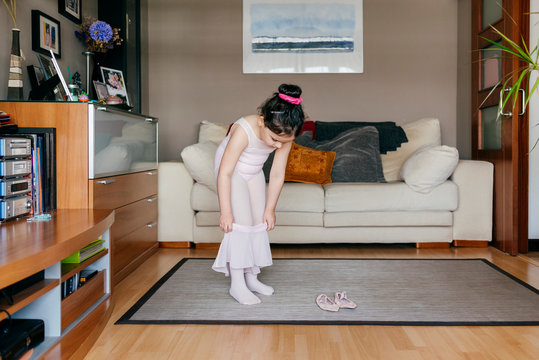 Cute little girl in light pink leotard and tights putting on skirt while standing near dance shoes in cozy living room at home