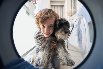 View from inside of washing machine of cute curly haired child in casual wear holding small dog and looking with interest inside