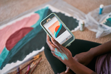 Crop unrecognizable African American female using app with picture sample on smartphone while learning painting at home during free time