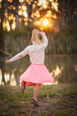 Little girl dancing by the river at sunset