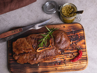 Fototapete - grilled beef steak with bone on a cutting board,  spices