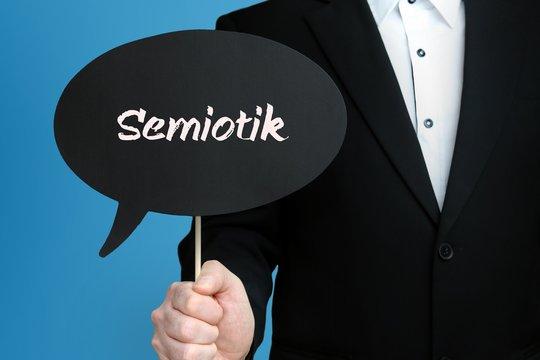 Semiotik. Mann im Anzug hält Sprechblase in der Hand. Der Text Semiotik steht im Schild. Blauer Hintergrund. Geschäftsmann für Business, Finanzen, Statistik