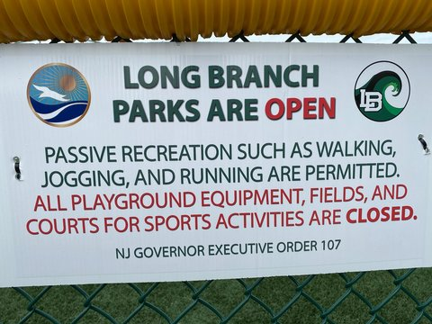 LONG BRANCH, NEW JERSEY - April 15, 2020: Sign caution playground fields sports are closed risk not sterilized after self-quarantine and social distancing covid-19 coronavirus pandemic.