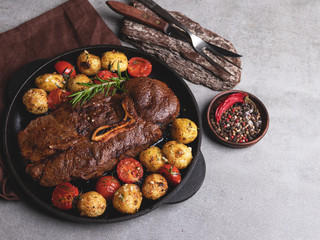 Fototapete - grilled beef steak with bone, roasted new potatoes  tomato with garlic in a pan