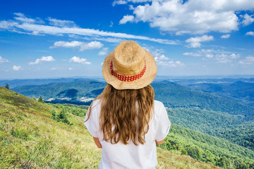 Bieszczady National Park in Poland landscape. Girl in straw hat watching the view from the hill peak. Summer holiday mountain trekking. Rural scenery lifestyle background. Fotomurales