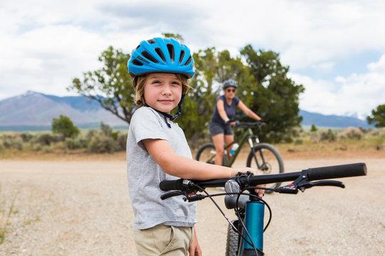 6 year old boy wearing bike helmet holding his mountain bike