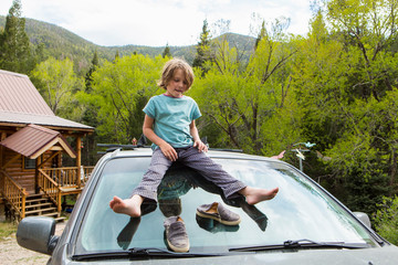 6 year old boy squatting on the front windshield of an SUV in a forest