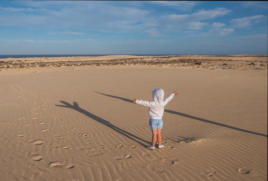 Child standing on sand in dunes Corralejo. Fuerteventura, Canary islands, Spain. October 2019