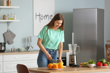 Young woman making smoothie in kitchen at home