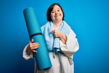 Young down syndrome fitness woman training yoga and pilates holding workout mat very happy pointing...