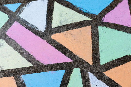 Brightly colored geometric shapes drawn in chalk along a side walk.