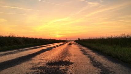 Foto auf Gartenposter Dunkelbraun Empty Road Amidst Landscape Against Orange Sky