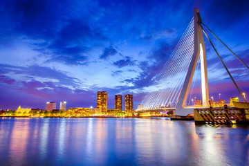 Dutch Travel Destination. View of Renowned Erasmusbrug (Swan Bridge) in Rotterdam in front of Port and Harbour. Picture Made At Dusk.