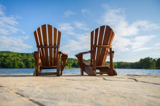 Two Adirondack chairs sit on a stone made pier, facing smooth waters of a lake in Muskoka, Ontario Canada. Image perspective from the pier level.