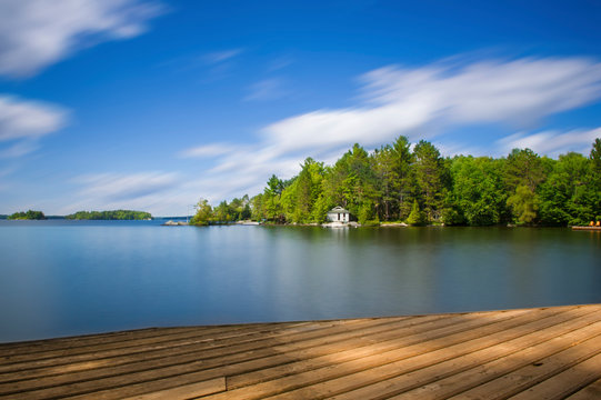 Wood dock in Muskoka facing a lake during a sunny summer day. Across the calm water there's a white cottage nested into the green trees.