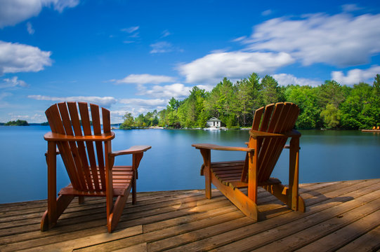 Two Muskoka chairs sitting on a wood dock facing a calm lake. Across the water is a white cottage nestled among green trees. There is a boat dock on the water in front of the cottage.