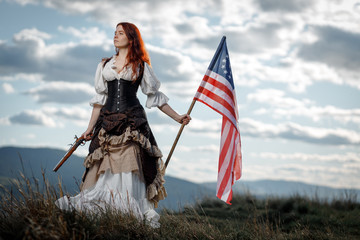 Girl in historical dress of 18th century with flag of United States. July 4 is US Independence Day. Woman of patriot freedom fighter in outdoor on background cloudy sky Wall mural