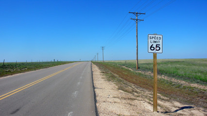 Fotomurales - Speed Limit 65 Sign And Electricity Pylon By Country Road Against Clear Blue Sky