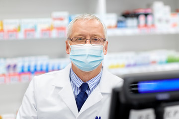 medicine, healthcare and people concept - senior apothecary wearing face protective medical mask...