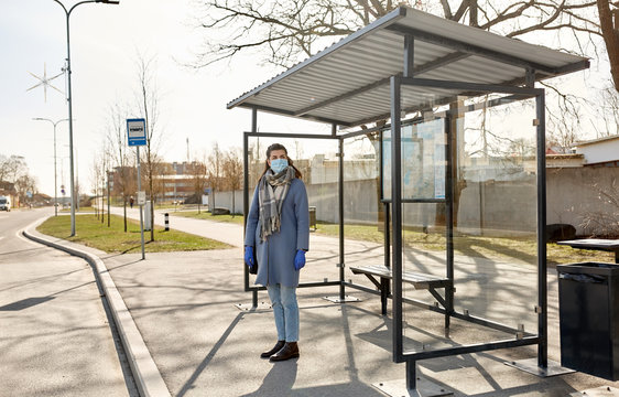 health, safety and pandemic concept - young woman wearing protective medical mask at bus stop in city