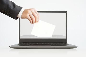 Voting Online Concept. Man Putting a Ballot into a Laptop.