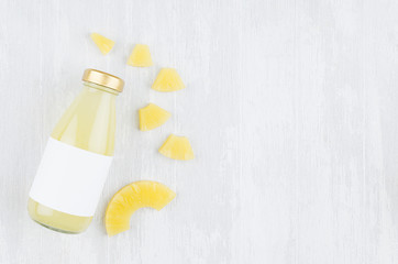 Organic pinapple yellow juice in glass bottle with blank label, sliced fruit on white wood background, top view, copy space, mock up for design, advertising.