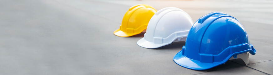 Fototapeta Banner Construction hard hat safety helmet workers in construction site for engineering protection head standard. Many hardhat helmet on row with copy space. Engineering Construction Concept obraz