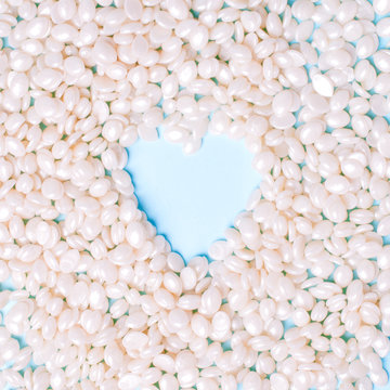 Depilatory Pearl Hard Wax Beans white color heart shape, concept of skincare bodycare, beauty industry, spa salon, hait remove materials. Discount banner, flyer, love your body, copy space