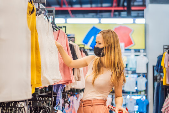 Woman in a clothing store in a medical mask because of a coronovirus. Quarantine is over, now you can go to the clothing store