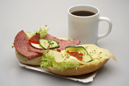 Zwei halbe Belegte Brötchen mit Salami und Käse, Tasse Kaffee
