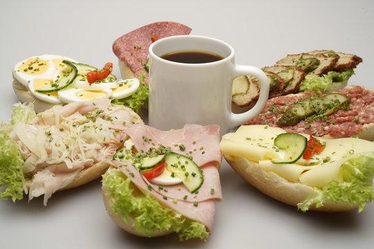 7 halbe Belegte Brötchen mit Salami und Käse, Tasse Kaffee