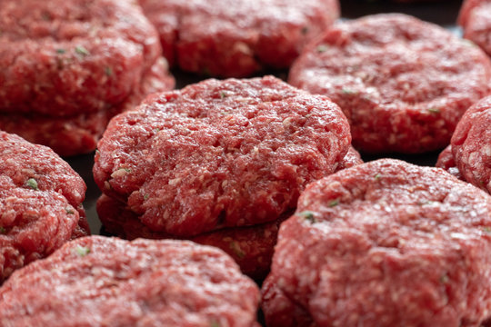 Multiple stacks of freshly processed raw hamburger patties on display in meat processing plant