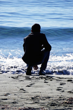 Rear View Of Man Crouching At Beach On Sunny Day