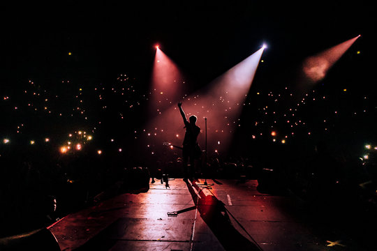 The vocalist of the group stands on the stage of the stadium. Stage view of crowd. cell phone lights. people holding mobile phones at a concert. silhouettes with their hands up. Dark background, smoke