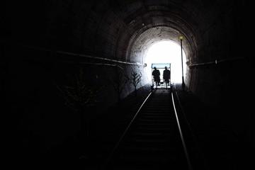 Keuken foto achterwand Tunnel Silhouette People Riding Handcar On Railroad Track In Tunnel