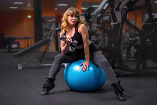 Senior female sitting on a fitness ball and lifting dumbbells. woman exercising with weights at gym.