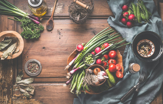 Healthy vegetarian eating and home cooking concept. Vegan ingredients on rustic wooden table with herbs and spices. Garden organic vegetables on wooden bowl. Top view. Paleo dieting.