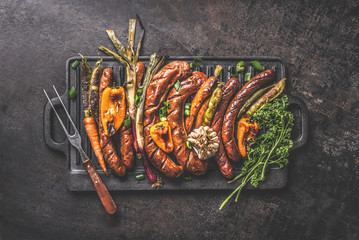 Various grilled meat sausages with roasted vegetables on cast iron grill pan with meat fork on dark...