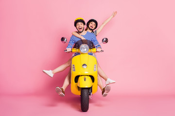 Portrait of nice attractive cheerful cheery glad carefree playful childish friends friendship driving vehicle without legs having fun fooling isolated on pink pastel color background