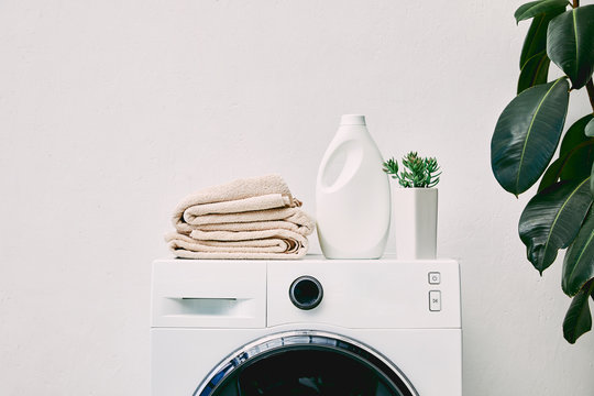 detergent bottle and towels on washing machine and green plant in bathroom