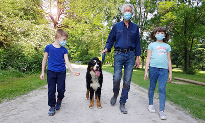 grandfather and grandson are walking in the park with the dog during Coronavirus Pandemia
