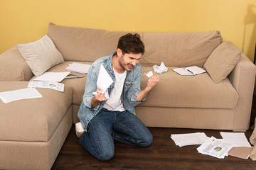 Keuken foto achterwand Hoogte schaal Aggressive man holding clumped paper near documents on couch and floor in living room
